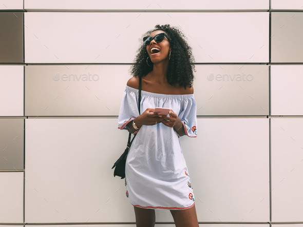 Cheerful black woman with mobile phone - Stock Photo - Images