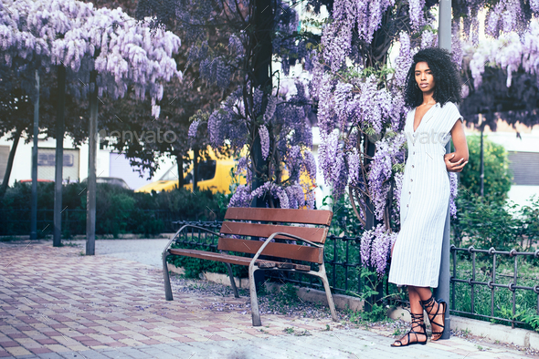 Young black woman surrounded by flowers - Stock Photo - Images