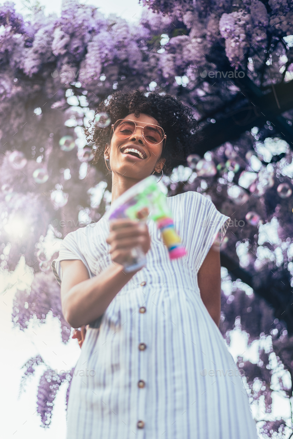 Happy young black woman surrounded by flowers - Stock Photo - Images