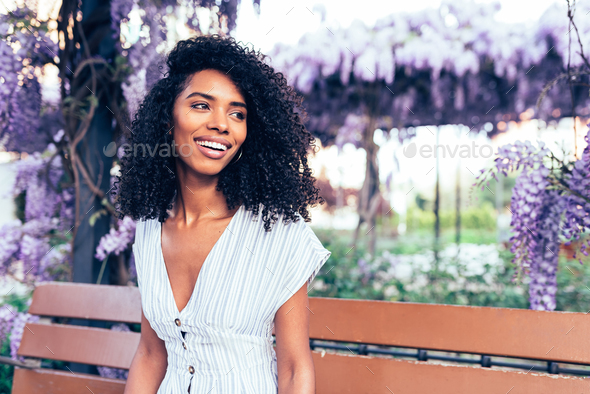 Happy young black woman sitting surrounded by flowers - Stock Photo - Images