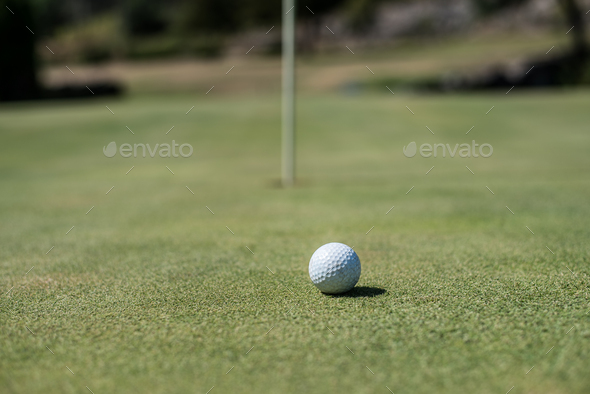 Golf field with white ball near the hole - Stock Photo - Images