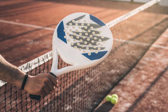 Man hand grabbing a padel racket - Stock Photo - Images