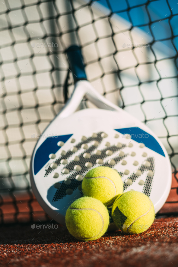 Padel blade racket resting on the net - Stock Photo - Images