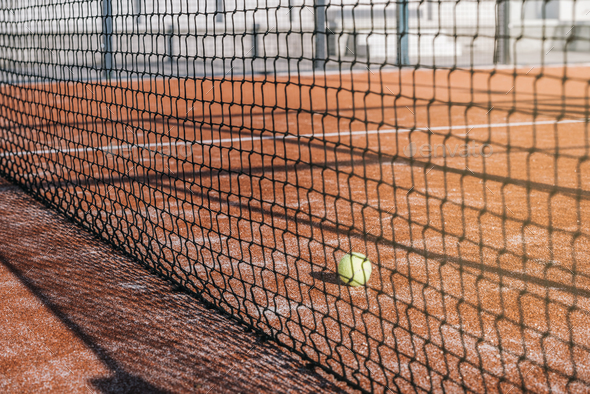 ball in net in a padel court with orange grass - Stock Photo - Images