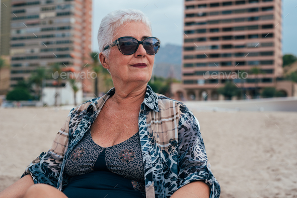 Elderly woman on the beach wearing sunglasses - Stock Photo - Images