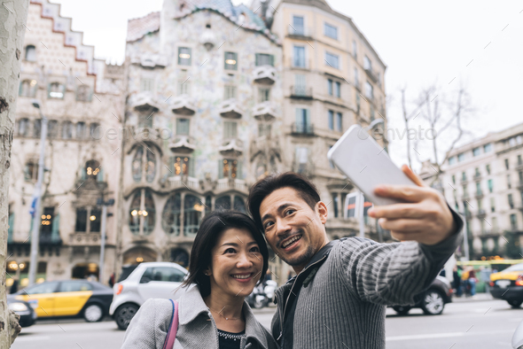 Asian tourist couple taking a selfie with a mobile phone - Stock Photo - Images