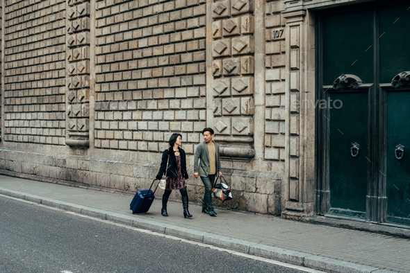 Asian happy tourist couple walking with suitcase - Stock Photo - Images