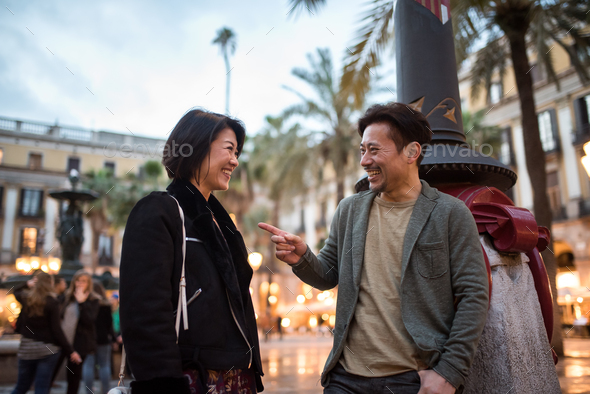 Asian happy tourist couple talking in a square - Stock Photo - Images