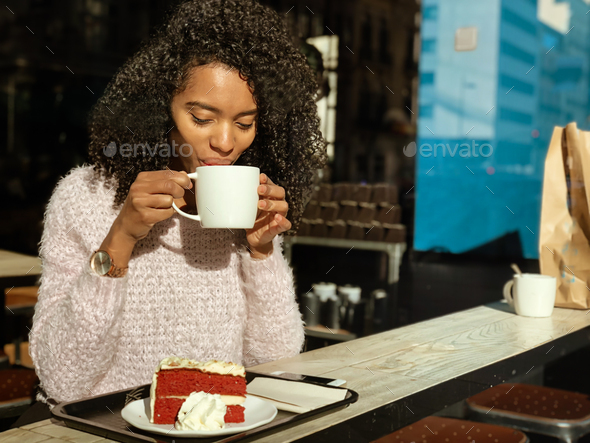 Black woman drinking a coffee and eating a cake - Stock Photo - Images