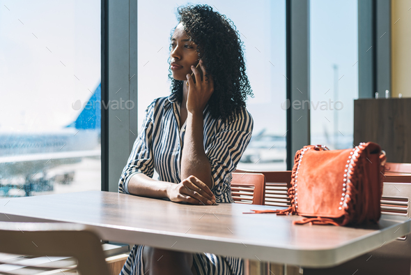 Woman on the mobile phone waiting for her flight at the airport - Stock Photo - Images
