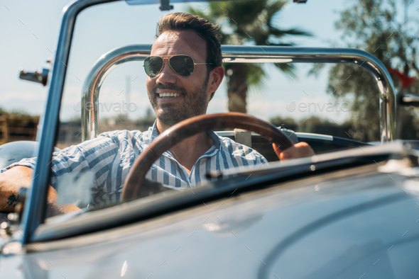Man driving a convertible vintage car - Stock Photo - Images