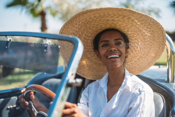 Black woman driving a vintage convertible car - Stock Photo - Images