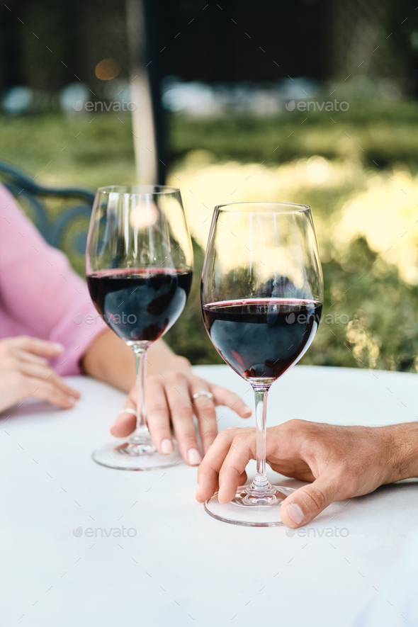 Close up photo of couple with glasses of red wine on romantic date in restaurant outdoor - Stock Photo - Images