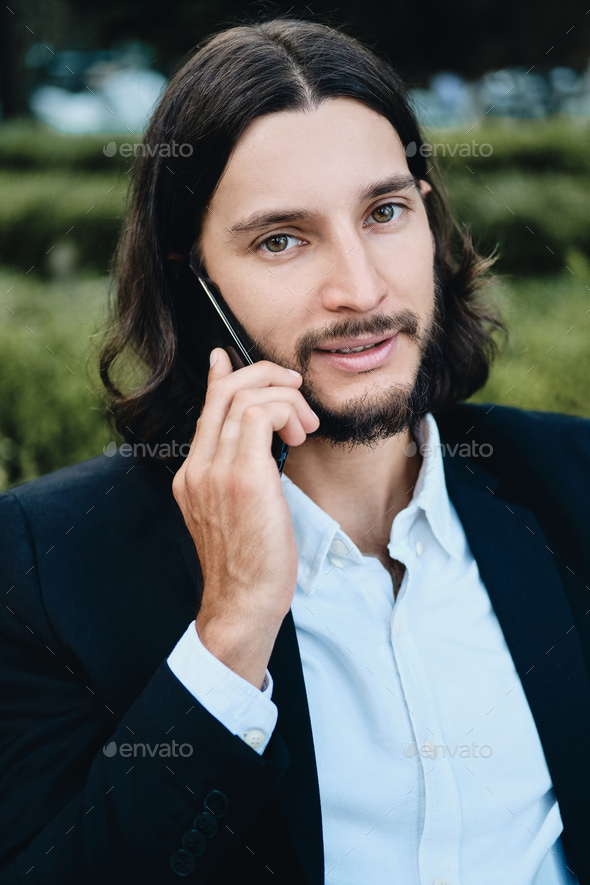 Attractive confident latin businessman looking in camera talking on cellphone in restaurant outdoor - Stock Photo - Images