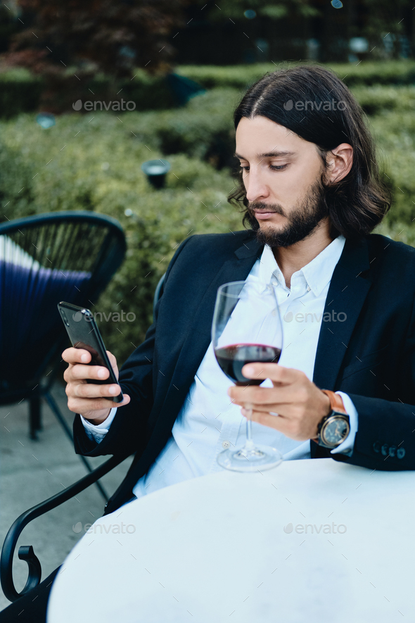 Confident latin businessman with glass of wine thoughtfully using cellphone in restaurant outdoor - Stock Photo - Images