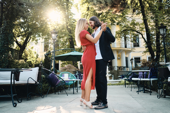 Young attractive romantic couple dreamily dancing on date in beautiful garden of restaurant - Stock Photo - Images