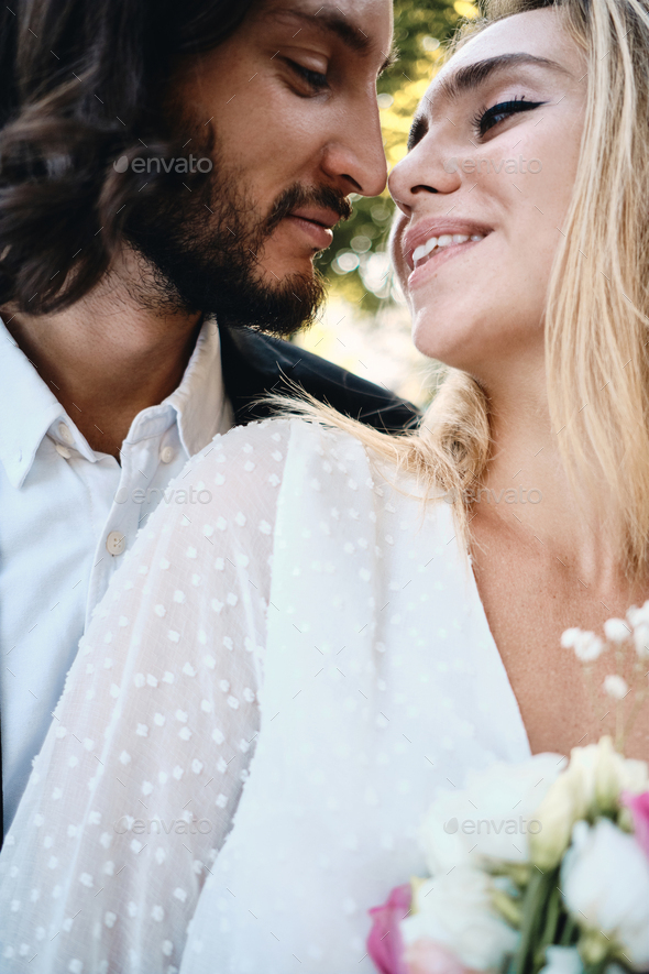 Portrait of beautiful bride and handsome groom dreamily kissing outdoor - Stock Photo - Images