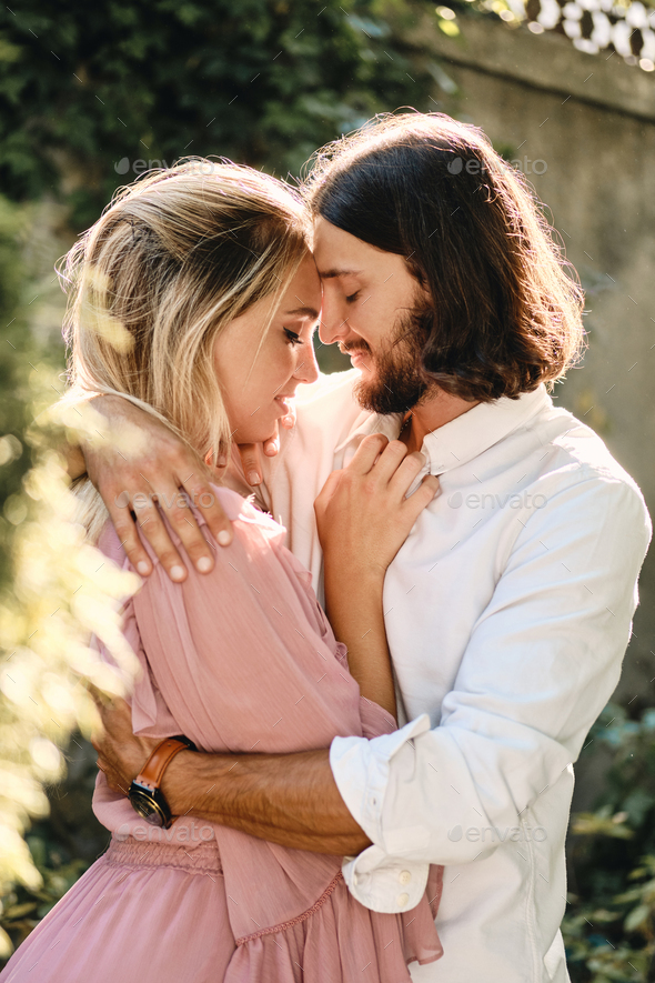 Portrait of young beautiful romantic couple sensually hugging each other on date outdoor - Stock Photo - Images