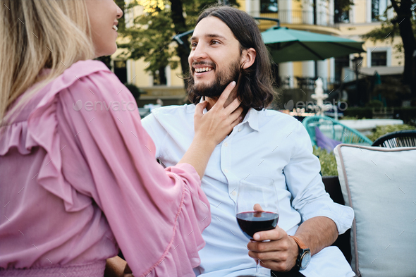 Latin man in shirt with glass of wine happily looking at girlfriend on romantic date in restaurant - Stock Photo - Images