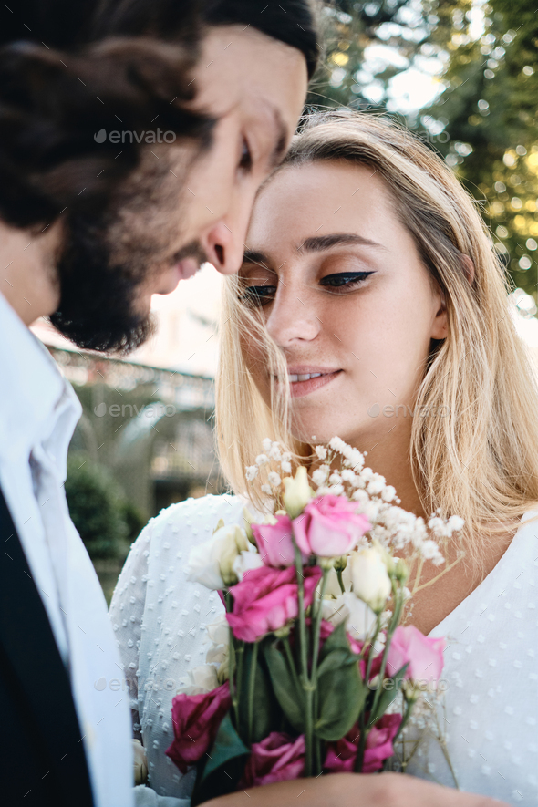 Beautiful blond bride and handsome brunette groom stranding with bouquet of flowers outdoor - Stock Photo - Images