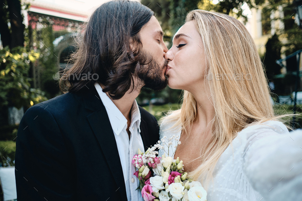 Young beautiful groom and bride sensually kissing taking selfie in garden of restaurant - Stock Photo - Images
