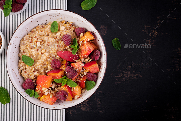 Oatmeal porridge with raspberry and peach on dark background. Healthy breakfast. - Stock Photo - Images