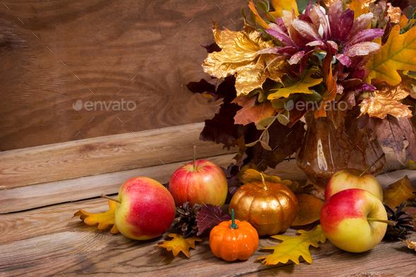 Fall centerpiece with purple flowers, golden pumpkin - Stock Photo - Images