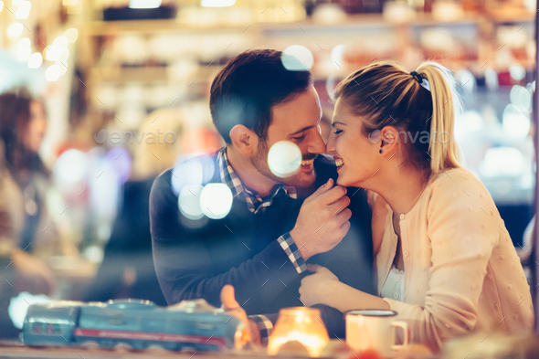 Romantic couple dating in pub at night - Stock Photo - Images