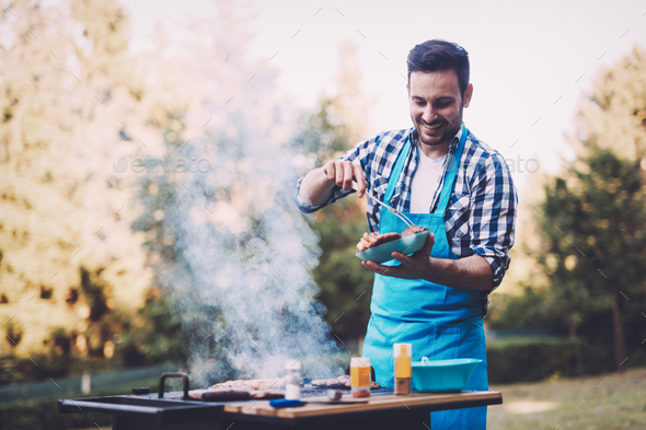 Handsome young man preparing barbecue in nature - Stock Photo - Images