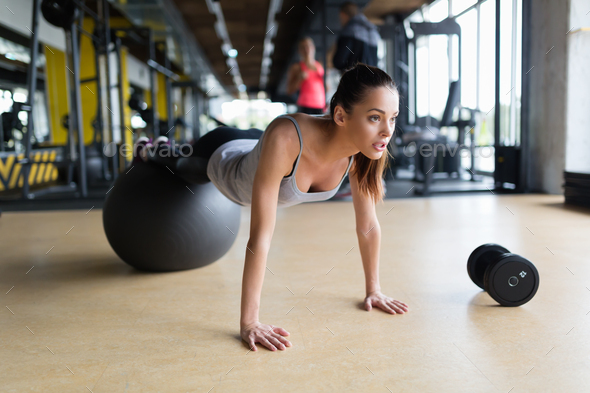 Young woman exercising with swiss ball in gym - Stock Photo - Images