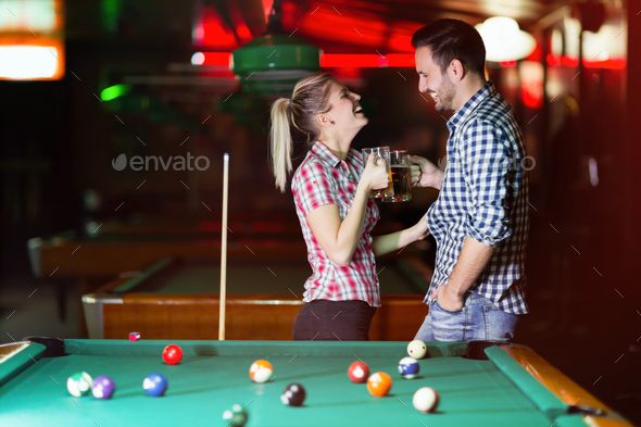 Couple drinking beer playing snooker on date - Stock Photo - Images