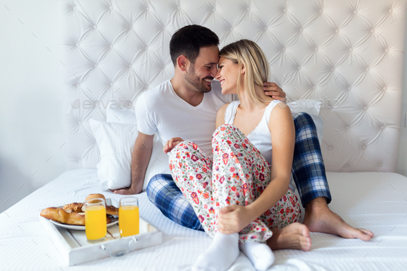 Young attractive couple having breakfast in bed - Stock Photo - Images