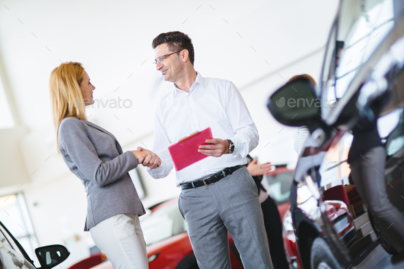 Successful businessman in a car dealership - sale of vehicles to customers - Stock Photo - Images