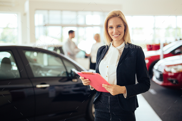 Picture of professional salesperson working in car dealership - Stock Photo - Images