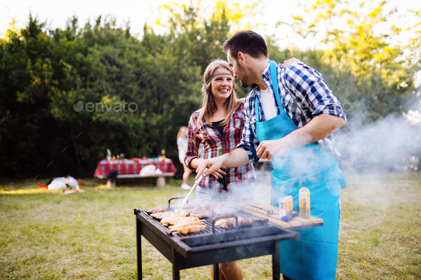 Happy students having barbecue on summer day - Stock Photo - Images