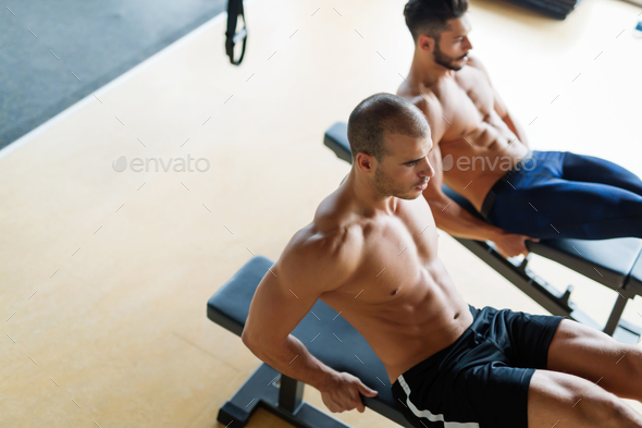Strong men are doing abs crunches on bench - Stock Photo - Images
