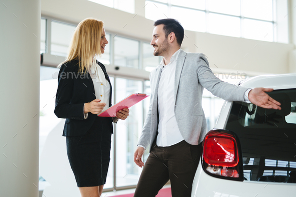 Young woman consultant in show room talking with client - Stock Photo - Images