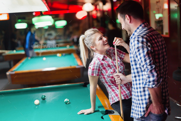 Young couple enjoying playing snooker on date - Stock Photo - Images