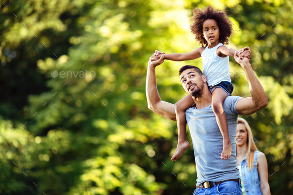 Portrait of young father carrying his daughter on his back - Stock Photo - Images