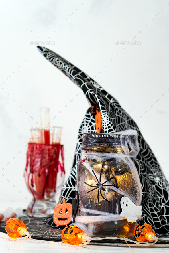 Halloween bloody glass with test tubes of tomato juice and Jar filled with orange string lights - Stock Photo - Images
