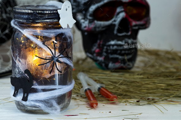 Jar filled with orange string lights in spooky room full in a black jar with a web and a spider on a - Stock Photo - Images