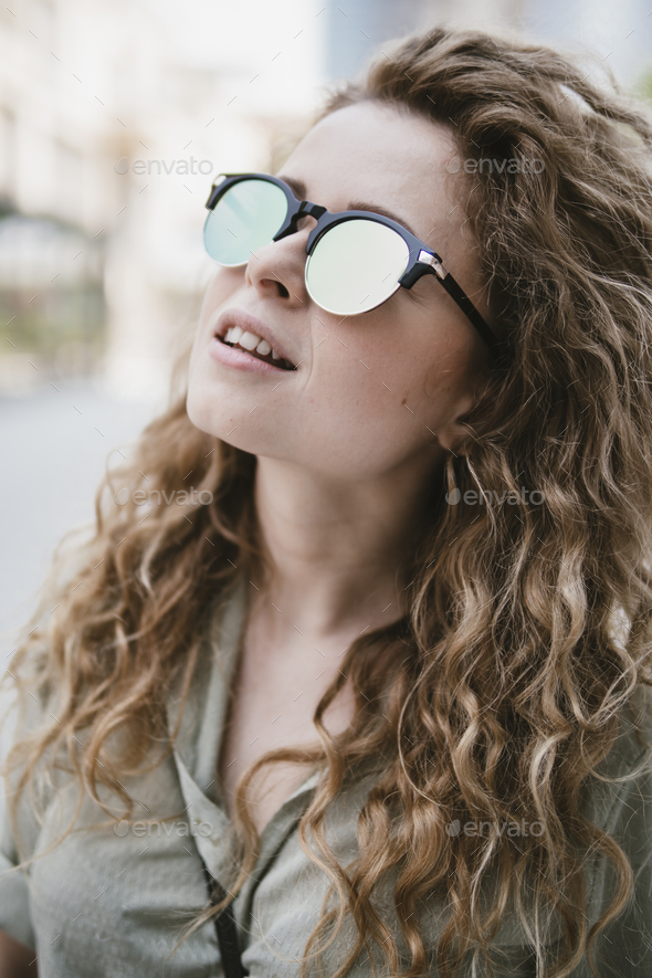 attractive young woman with reflective sunglasses - Stock Photo - Images