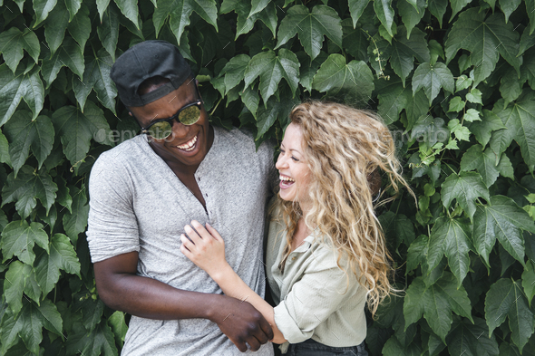mixed race couple hugging in nature - Stock Photo - Images