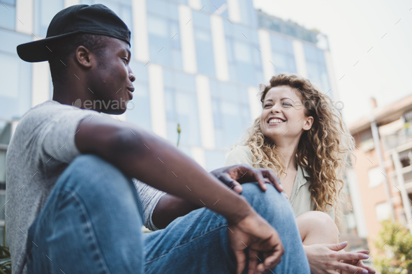 mixed race friends chatting on a bench - Stock Photo - Images