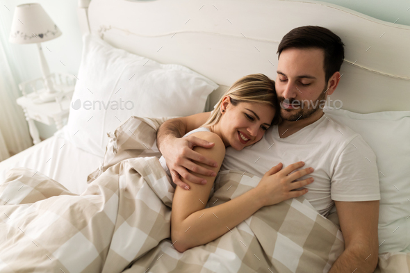 Young attractive couple having romantic time in bed - Stock Photo - Images