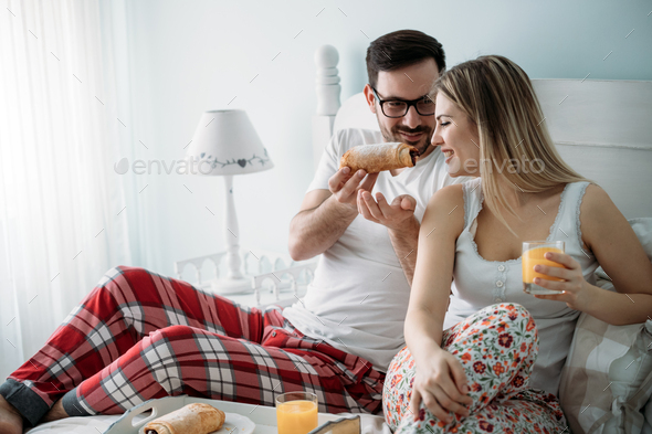 Portrait of young loving couple in bedroom - Stock Photo - Images