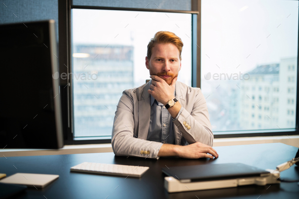 Portrait of young businessman sitting at desk - Stock Photo - Images