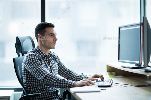 Portrait of young businessman working on computer - Stock Photo - Images