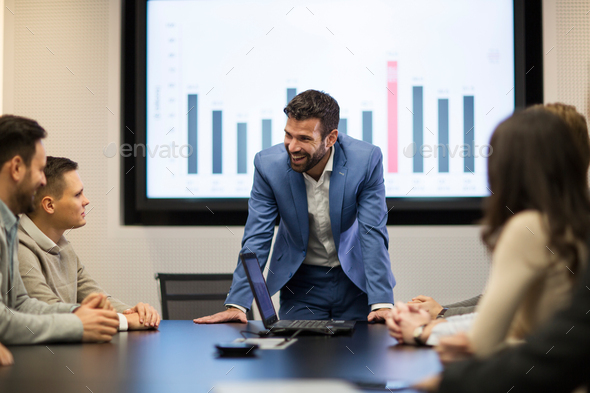 Young attractive businessman showing presentation to his colleagues - Stock Photo - Images