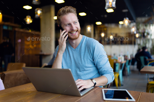 Young man having phone call in coffee shop - Stock Photo - Images